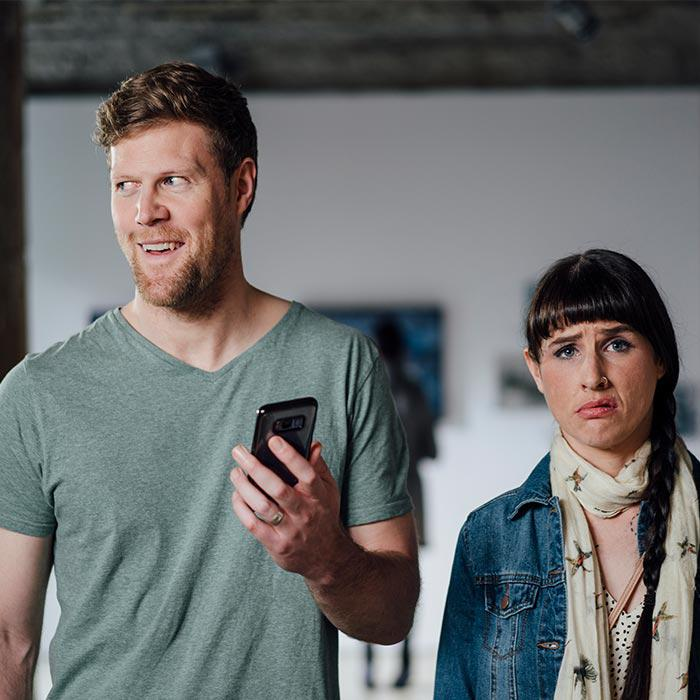 Man looking at his mobile phone in art gallery, while his partner looks at the camera