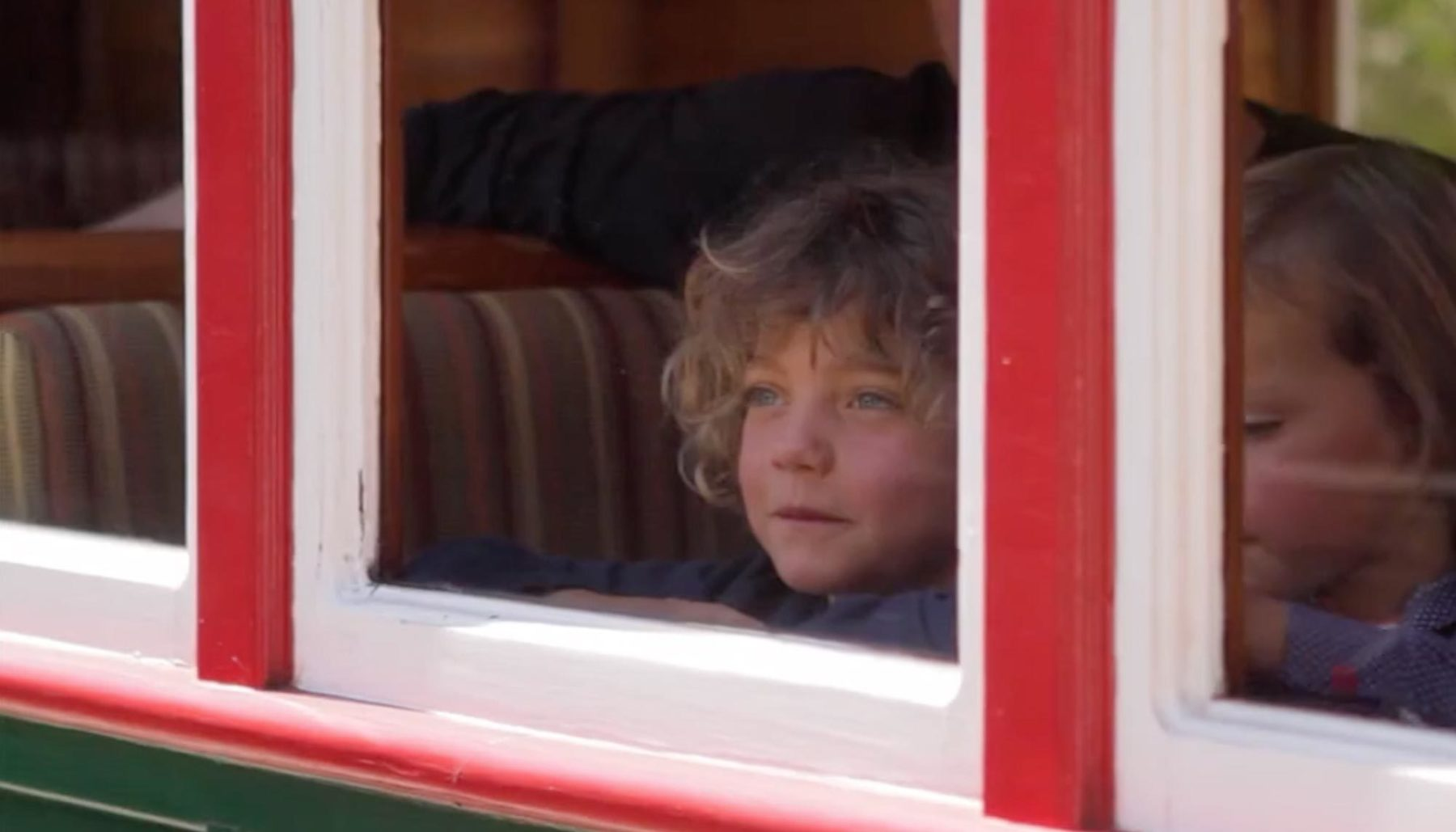 Young boy looking out of carriage window on West Coast Wilderness Railway
