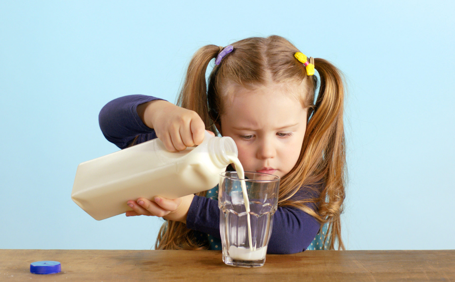 Cute child concentrating on pouring milk