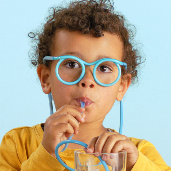 Cute kid drinking milk through glasses
